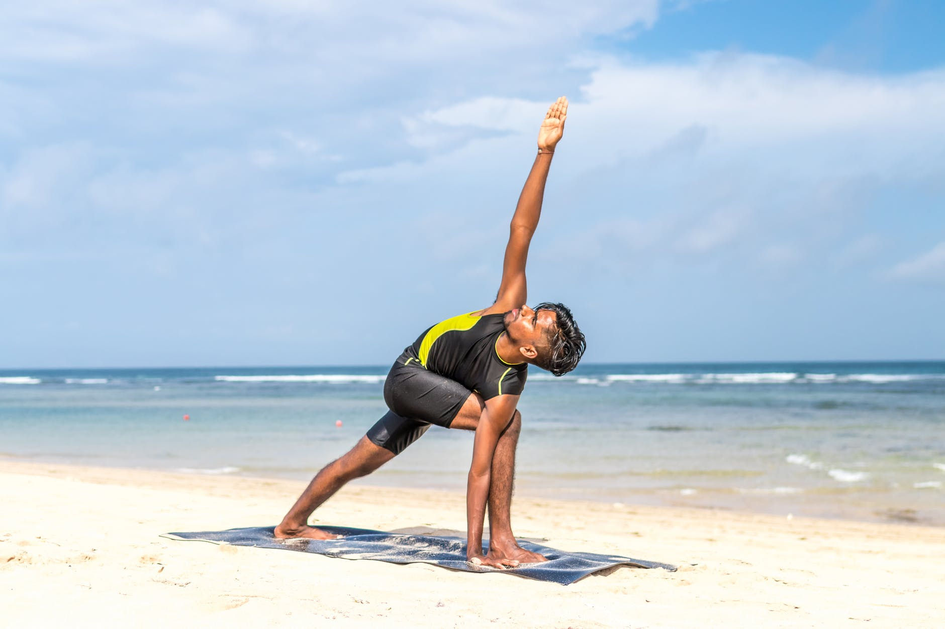 man doing yoga pose on blue mat beside seashore